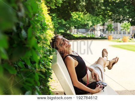 Pensive pretty young blonde girl sitting on a park bench