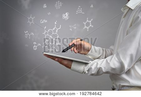 Man scientist with tablet pc and stylus or pen working with chemical formulas on gray background.