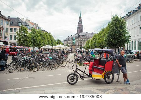 Copenhagen Denmark - Jul 29 2015: A driver of tricycle rickshaw waits for customers in Copenhagen city center on July 29 2015.