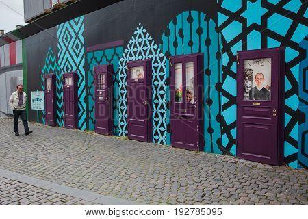 Copenhagen Denmark - July 29 2015: An unidentified man walks along the temporary wall with artistic installation of purple doors in Copenhagen city centre.