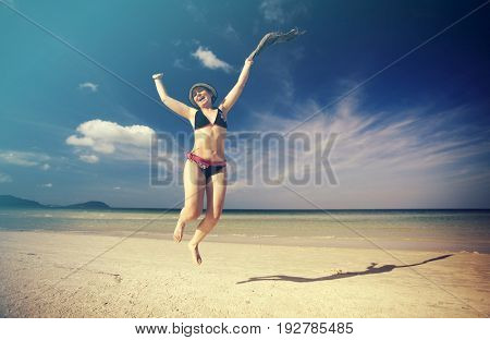 Beautiful young woman jumping on tropical beach with a colored scarf