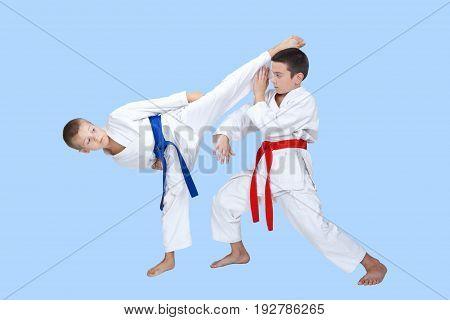 Two boys train a circular kick and block