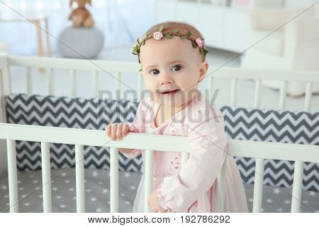 Cute little girl standing in crib at home