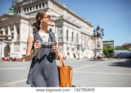 Young female tourist with photo camera in front of the famous Opera house in Frankfurt city