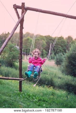 Little girl flying on swing in countryside at Sunset. Childhood Freedom Happy Summer Outdoor