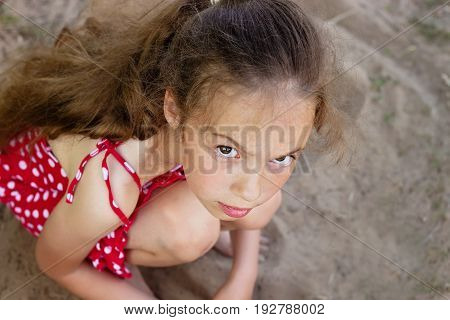Beautiful Sad little girl is looking with serious face at camera.