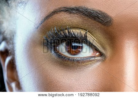 Extreme close up of african female eye with professional make up.