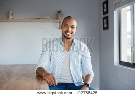 Smiling young african american man sitting on table at home. Portrait of black guy in casual looking at camera indoor. Carefree happy man relaxing at home.
