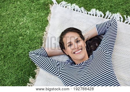 Portrait of latin woman relaxing on blanket at park. Top view of happy mature woman lying on blanket on grass. Hispanic woman lying down with hand behind head and looking at camera with copy space.
