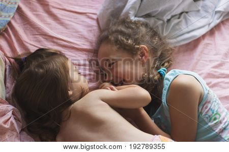 Kids playing in bed after wake up. A cute children enjoys sunny morning. Soft light and soft focus to feeling relax and comfortable.