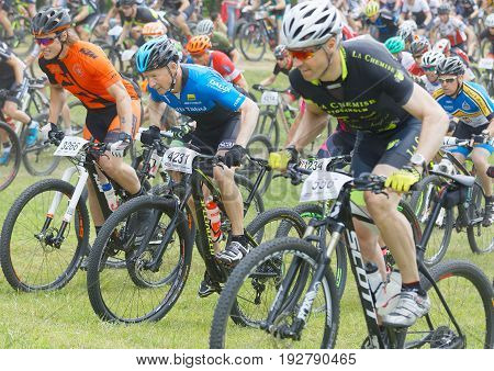 STOCKHOLM SWEDEN - JUNE 11 2017: Side view of group of fighting male mountain bike cyclists cycling uphill at Lida Loop Mountain bike Race audience in background. June 11 2017 in Stockholm Sweden