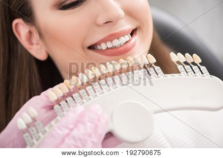 Close up dental crown situating near mouth of woman in dental apartment