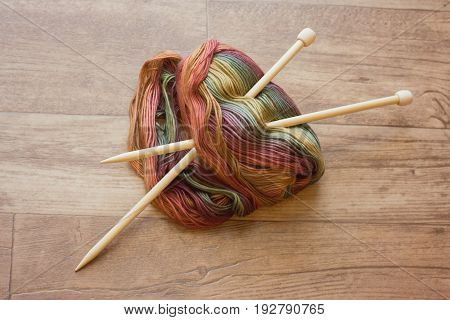 bamboo knitting needles inserted into a skein of beautiful yarn