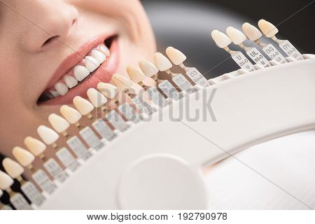 close up mouth of female with dental crown situating near it in odontology
