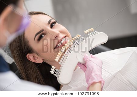 Top view girl expressing cheerfulness while sitting in chair in stomatology. Doctor choosing right implants of teeth. Health concept