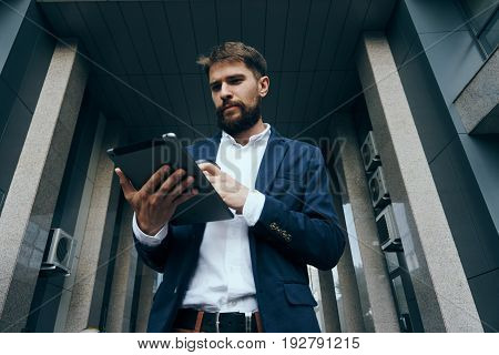 Businessman with a beard holding a tablet on the street, work, office, city.
