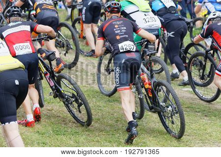 STOCKHOLM SWEDEN - JUNE 11 2017: Group of male mountain bike cyclists running with cycles uphill at Lida Loop Mountain bike Race. June 11 2017 in Stockholm Sweden