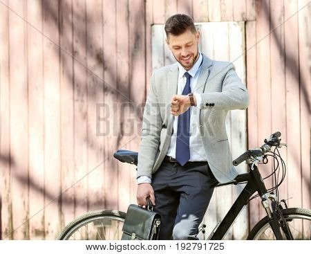 Handsome young businessman looking at watch while standing near bicycle outdoors on sunny day