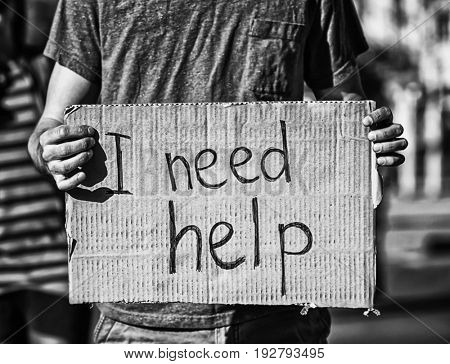 Poverty concept. Poor man holding cardboard sheet with text I NEED HELP on street
