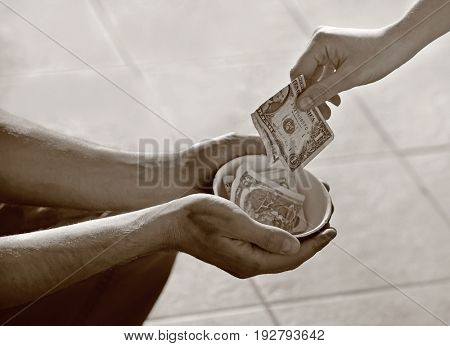 Poverty concept. Woman giving money to beggar on street, closeup