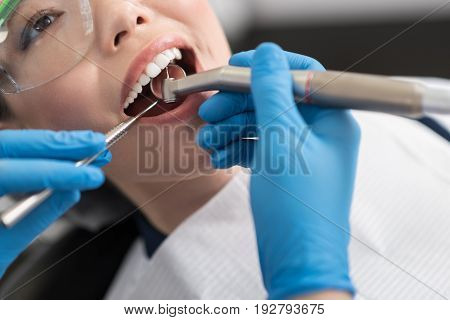 Close up wide open mouth of happy female. Doctor drilling it in stomatological room
