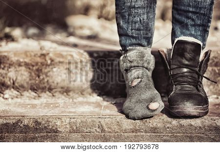 Poverty concept. Poor woman wearing tatter sock and one boot