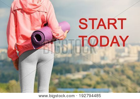 Fitness quotes. Text START TODAY and young woman with mat on cityscape background