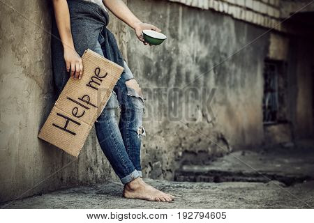 Poverty concept. Poor woman begging for help and money on street