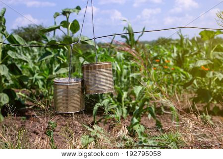 Two cans tied to scare wild animals on the farm