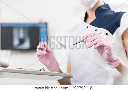 Close up stomatologist hands keeping instruments. She preparing them for treatment client