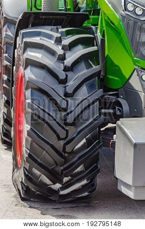 A large black tractor wheel with a tread designed for work on the farm