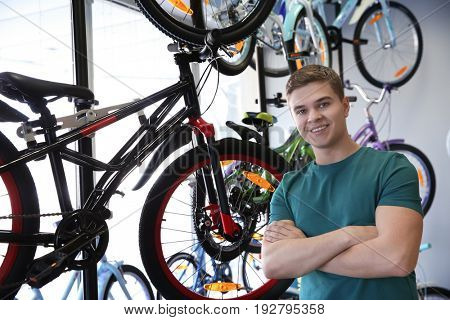 Smiling young man standing in bicycle shop