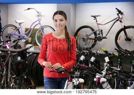 Smiling girl standing in bicycle shop