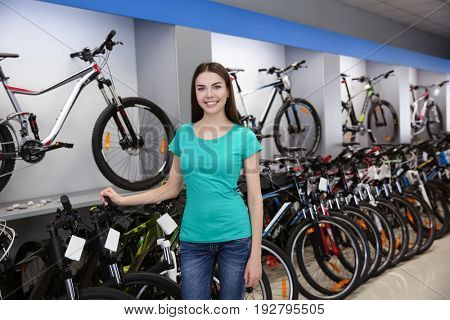 Smiling girl checking bicycle in shop