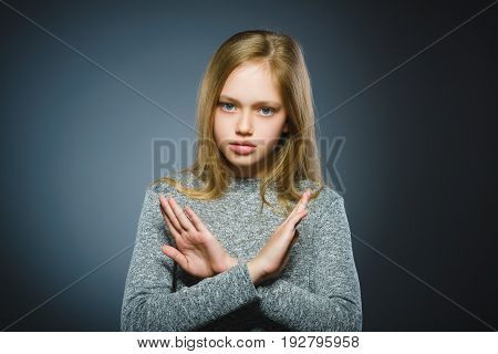 Serious girl making X sign with her arms to stop doing something.