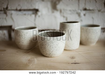 Glazed white ceramic rustic cups on wooden shelf in pottery workshop