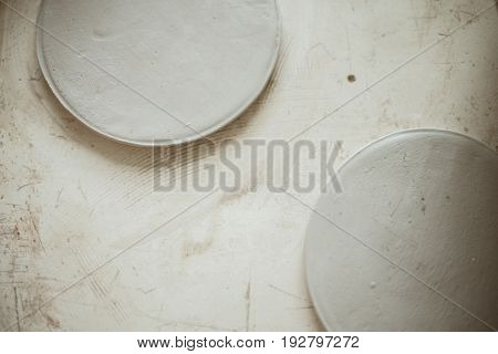 Raw clay grey round workpiece for plates on scratched background table. Focus on plate.