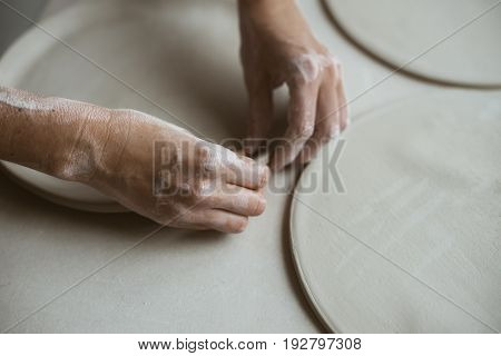 Woman's hands makes clay plates in pottery workshop close up view; focus on stained hand