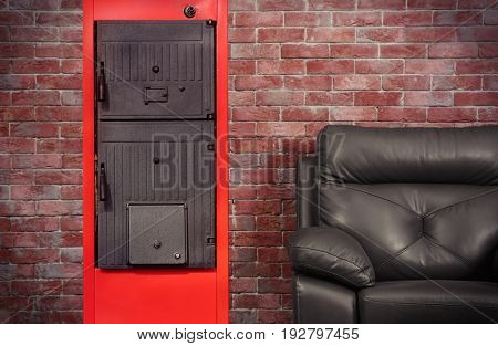 Energy savings concept. Solid fuel boiler and armchair against brick wall background
