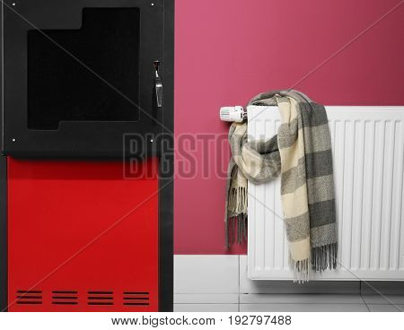 Energy savings concept. Solid fuel boiler and radiator with scarf on color wall background