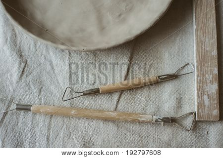 Pottery tools with wooden holders and raw clay plate on table with industrial fabric in pottery studio