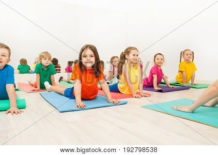 Group of happy kids, 5-6 years old boys and girls, stretching their backs on yoga mats during gymnastics in sports club