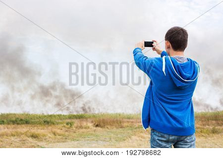 the man filming strong smoke over the burning fields of ripe wheet during the strong heat and a drought in the summer.