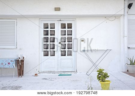 white house facade with flowerpots, clothing rack dryer, chair and table