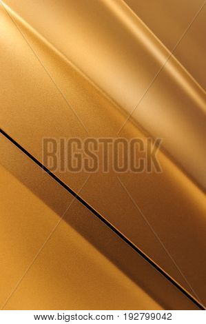 Surface of bronze sport sedan car, detail of metal hood and fender of vehicle bodywork