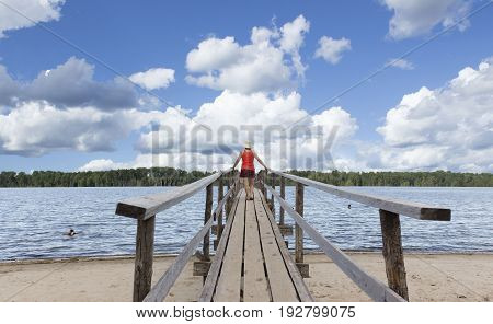 horizontal image of a woman in shorts and top walking over a long wooden bridge over a lake and watching kids swimming.