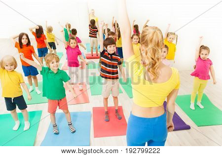 Group of age-diverse kids doing gymnastic exercises with female instructor in gym