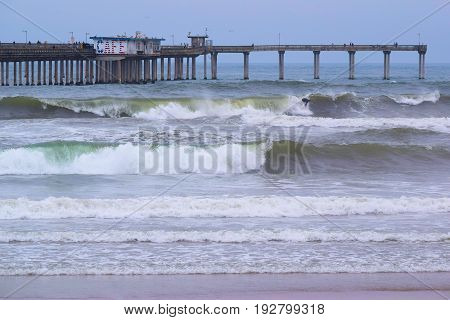 June 22, 2017 in Ocean Beach, CA:  Waves crashing onshore with a large pier beyond including a café on the pier taken in Ocean Beach, CA where locals and tourists can walk on the pier and dine at the cafe