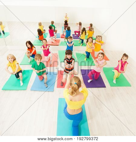Happy kids standing in two lines and doing kneeling exercises during gymnastic group session with female instructor