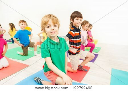 Portrait of happy kids practicing gymnastics, doing knee bending exercises on mats, against blanked background